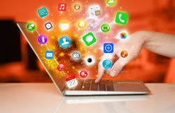 Hand pressing modern laptop with mobile app icons and symbols. Comming out Royalty Free Stock Photography