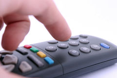 Hand pressing remote control button  on white Royalty Free Stock Images