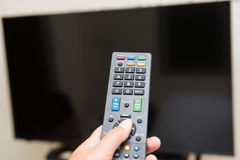 Hand pressing remote control to turn on the TV Royalty Free Stock Photo