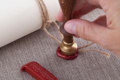 Hand pressing seal stamp to the rope of document with wax seal. Horizontal Stock Image