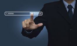 Hand pressing search button over blue background, searching syst Stock Image