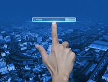 Hand pressing search www button over street, expressway and city Royalty Free Stock Image