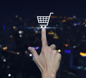 Hand pressing shopping cart icon over blurred light city tower b Royalty Free Stock Photos