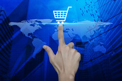 Hand pressing shopping cart icon over map and city tower, Shoppi Stock Image