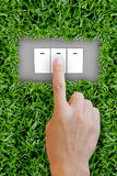 Hand pressing switch button. In green grass Royalty Free Stock Photos