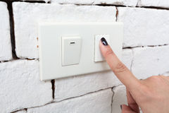 Hand pressing switch off to save energy. Stock Photo
