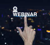 Hand pressing webinar icon over blur night city tower background. Seminar online concept Stock Photo