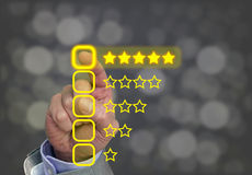Hand pressing yellow five star button of performance rating. On dark background with bokeh Stock Images