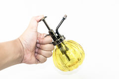 Hand pressuring yellow spray glass bottle isolate Stock Image