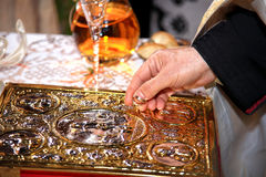Hand of a priest holding wedding rings Stock Photography