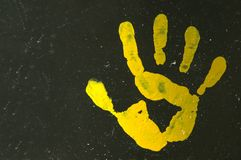 Hand print. A yellow painted open hand print with five fingers on a black background Stock Photo