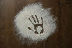 Hand print in flour. Hand print on floured wooden surface Royalty Free Stock Image
