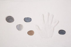 Hand print in the sand with five stones for meditation concepts. Royalty Free Stock Image