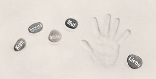 Hand print in the sand with stones. German words for power, harm Royalty Free Stock Image
