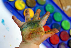 Hand printing. A child doing hand prints with colored paint stock photos