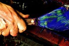 Hand at the Printing Press. Close up a hand scraping ink at a printing press Stock Photography