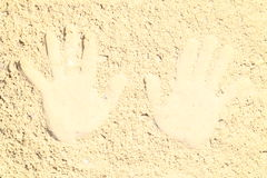 Hand prints. Imprints of hands on the sea-wet and yellow sand Royalty Free Stock Images