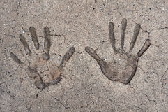 Hand Prints. Overhead shot of two hands prints in cracked cement Stock Image