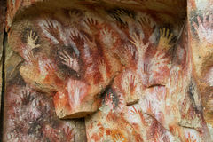 Hand prints on a cave wall. Cave of Hands in Argentina, cueva de las manos. Handprints made with red, yellow and black colour paint of ancient people on the wall stock photos