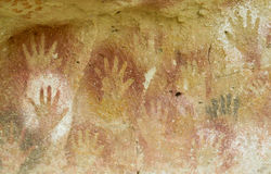 Hand prints on a cave wall. Cave of Hands in Argentina, cueva de las manos. Handprints made with red, yellow and black colour paint of ancient people on the wall Stock Image