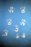 HAND PRINTS. Child hand playing with traces of white paint on a blue background, leaving their fingerprints stock photography