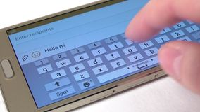 Hand prints a message hello on modern mobile phone, close up, white stock video footage