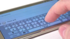Hand prints a message on modern mobile phone, close up, white stock footage