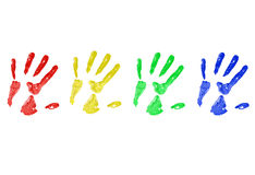 Hand Prints in Paint. Multi colored hand prints on a white canvas - red, yellow, green, blue stock image