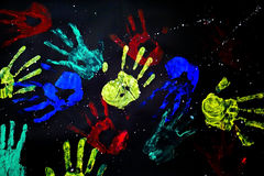 Hand prints. In rainbow on black background stock photography