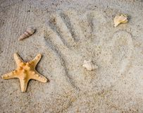 Hand prints in the sand. With shells and starfish stock photo