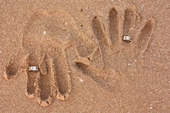 Hand prints on the sand husband and wife. Hand prints on the beach sand with wedding rings Stock Photography
