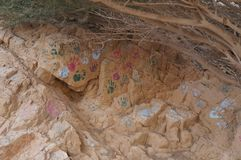 Hand prints of unknown people on rock in desert. Hand prints of unknown people on the rock in desert royalty free stock images
