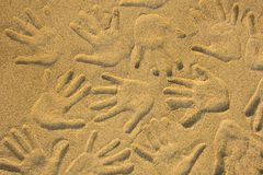 Hand prints on yellow sand close up. natural surface texture. A hand prints on yellow sand close up. natural surface texture royalty free stock photo