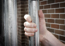 Hand on prison bars. And brick wall visible in background Royalty Free Stock Photo