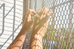 Hand of prisoner in jail. Catching mesh cage and  want to freedom Stock Photography