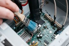 Hand of professional repairman holding a cleaning brush inside old personal computer. PC cleaning and maintenance concept, close u. P view stock image