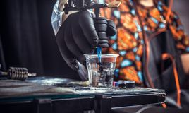 Hand of professional tattooer with a tattoo gun. Hand of tattoo artist with a tattoo machine royalty free stock image