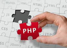 Hand of programmer holds puzzle with PHP programming language. Written Stock Image