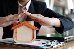 Hand protecting house model. home insurance, safety & security c. Woman& x27;s hand protecting house model. home insurance, safety & security concept Stock Images