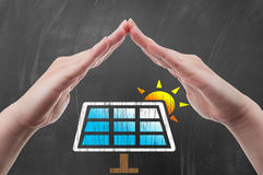 Hand protecting solar power panel draw on blackboard Stock Photography