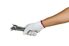 A hand with protection glove holding various spanners Stock Photography