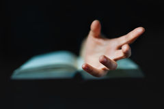 Hand protruding out from an open book Stock Images