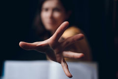 Hand protruding out from an open book Royalty Free Stock Photo