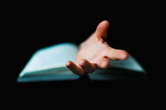 Hand protruding out from an open book Royalty Free Stock Image