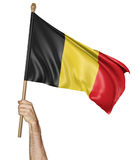 Hand proudly waving the national flag of Belgium. Rendered in 3D and isolated on a white background royalty free illustration