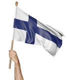 Hand proudly waving the national flag of Finland. Isolated on a white background Royalty Free Stock Images