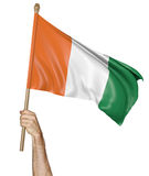 Hand proudly waving the national flag of Ivory Coast. Isolated on a white background Royalty Free Stock Photo