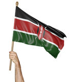 Hand proudly waving the national flag of Kenya. Isolated on a white background royalty free stock photography