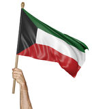 Hand proudly waving the national flag of Kuwait Royalty Free Stock Photography