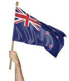 Hand proudly waving the national flag of New Zealand, 3D rendering. A young man& x27;s hand proudly raising the country flag of New Zealand high into the air Stock Photo